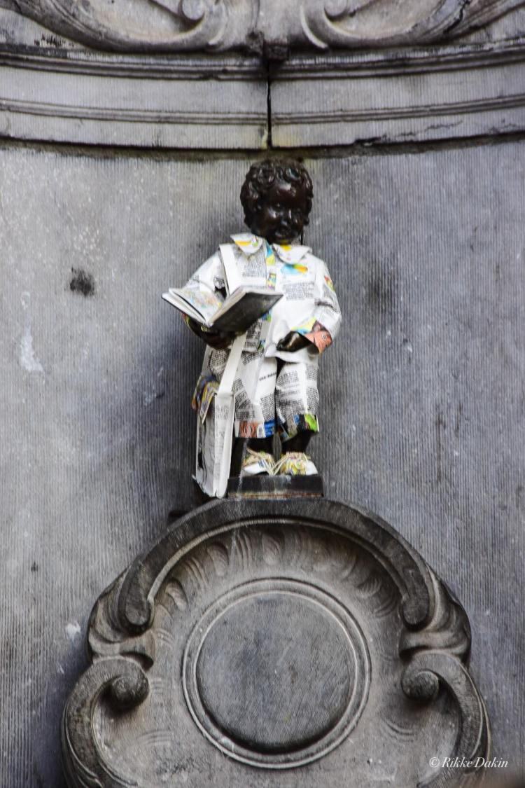Manneken Pis is pretty much what he sounds like. Sometimes the locals dress him up. We found him in a flash newspaper suit. Look closely, he is peeing.