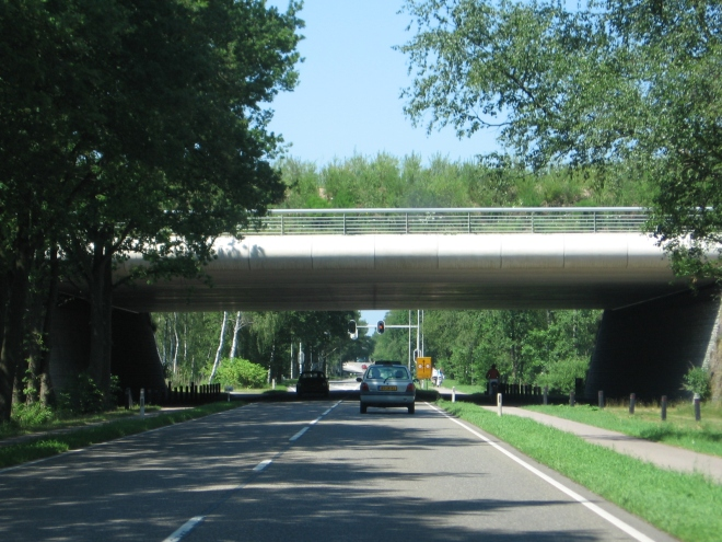 Driving under the ecoduct. Note the trees above the road. The path flanking the road is for bikes, so they are also safe. (Naturrbrug Zanderij Crailo, one of our local ecoducts.)  Photo Credit: Door M.Minderhoud - Eigen werk, CC BY-SA 3.0, https://commons.wikimedia.org/w/index.php?curid=872710